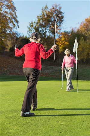Full length rear view of senior female golfer playing with friend on golf course Stock Photo - Premium Royalty-Free, Code: 698-07611466