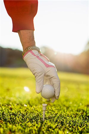Woman placing golf ball on tee Stock Photo - Premium Royalty-Free, Code: 698-07611474