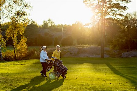 Senior women walking with golf bags on grassy area Stock Photo - Premium Royalty-Free, Code: 698-07611476
