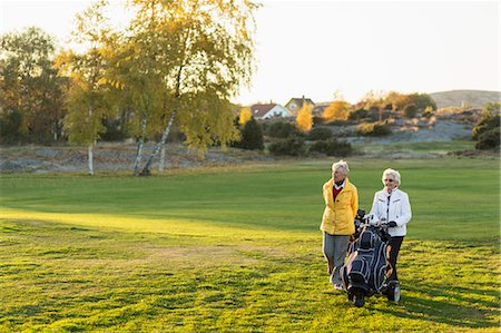 Senior female friends walking with golf bags on course Stock Photo - Premium Royalty-Free, Code: 698-07611477