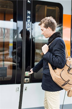 Side view of young businessman pressing door button while boarding train Stock Photo - Premium Royalty-Free, Code: 698-07611478