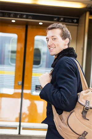 Portrait of smiling young businessman with backpack on railroad station Stock Photo - Premium Royalty-Free, Code: 698-07611480