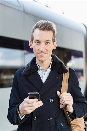 Portrait of confident young businessman holding cell phone on railroad station Stock Photo - Premium Royalty-Free, Code: 698-07611482