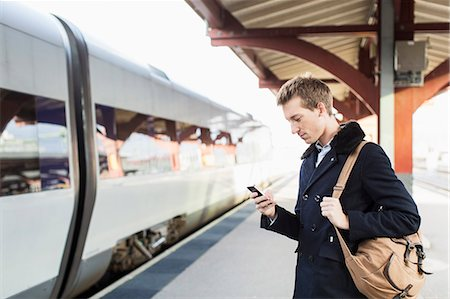 Side view of young businessman using cell phone on railroad station Stock Photo - Premium Royalty-Free, Code: 698-07611483