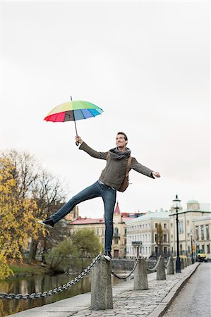 Full length of businessman with umbrella balancing on bollard outdoors Stock Photo - Premium Royalty-Free, Code: 698-07611495