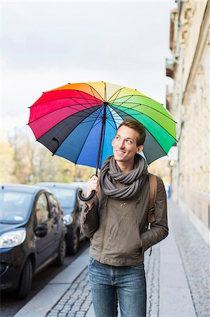 Young businessman with umbrella walking on footpath Stock Photo - Premium Royalty-Free, Code: 698-07611496