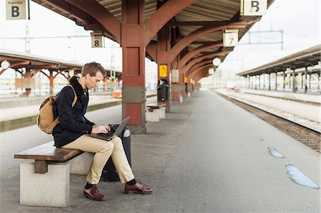 people sitting on bench - Full length side view of young businessman using laptop on railroad station Stock Photo - Premium Royalty-Free, Code: 698-07611492