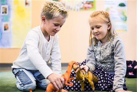Kids playing with toy dinosaurs in kindergarten Stock Photo - Premium Royalty-Free, Code: 698-07611546
