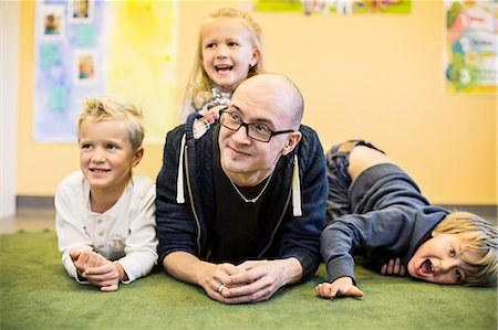 dece11 - Portrait of playful children with teacher in kindergarten Stock Photo - Premium Royalty-Free, Code: 698-07611548