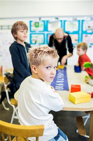 Portrait of confident kindergarten boy in art class with teacher and friends Stock Photo - Premium Royalty-Free, Code: 698-07611556