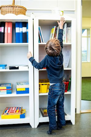 reaching - Rear view of boy reaching for container on shelf in kindergarten Stock Photo - Premium Royalty-Free, Code: 698-07611559