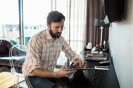 Businessman touching digital tablet in hotel room Stock Photo - Premium Royalty-Free, Code: 698-07611576