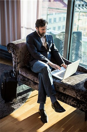 Businessman using laptop in hotel room Stock Photo - Premium Royalty-Free, Code: 698-07611570