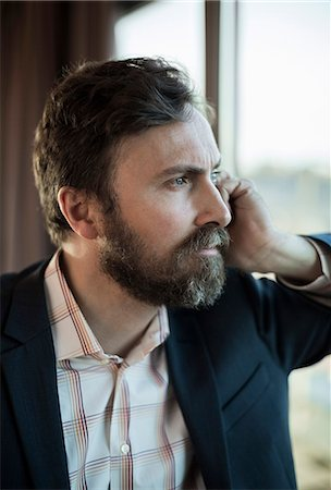 portrait looking away - Thoughtful businessman leaning on window in hotel Stock Photo - Premium Royalty-Free, Code: 698-07611573