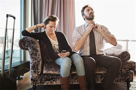 Business couple relaxing on chaise longue in hotel room Stock Photo - Premium Royalty-Free, Code: 698-07611588