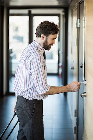 Businessman opening hotel door with cardkey Stock Photo - Premium Royalty-Free, Code: 698-07611590