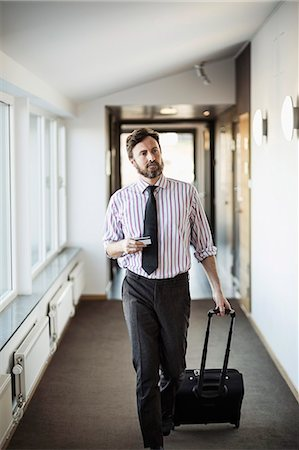 Businessman with suitcase walking in hotel corridor Stock Photo - Premium Royalty-Free, Code: 698-07611591