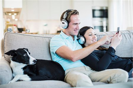 Couple listening to headphones with dog sitting on sofa Stock Photo - Premium Royalty-Free, Code: 698-07611620