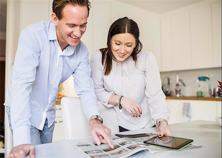 Happy couple with digital tablet looking at catalog in kitchen Stock Photo - Premium Royalty-Free, Code: 698-07611635