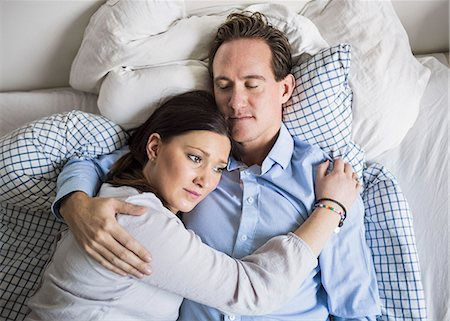 High angle view of sad woman embracing man while lying in bed Stock Photo - Premium Royalty-Free, Code: 698-07611630
