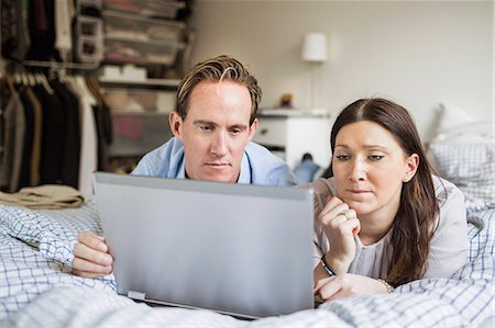 Couple using laptop while lying in bed at home Stock Photo - Premium Royalty-Free, Code: 698-07611631