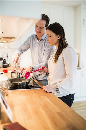 Couple cooking together in kitchen Stock Photo - Premium Royalty-Free, Code: 698-07611632