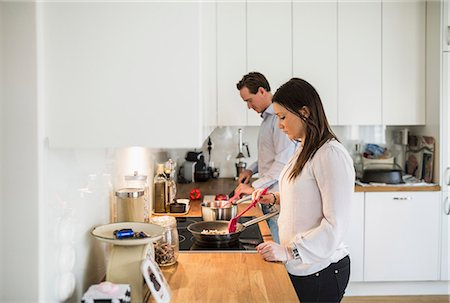 Couple preparing food together in kitchen Stock Photo - Premium Royalty-Free, Code: 698-07611633