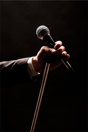 Hand holding microphone over black background Stock Photo - Premium Royalty-Free, Code: 698-07611694