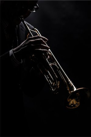 Musician playing trumpet over black background Stock Photo - Premium Royalty-Free, Code: 698-07611693