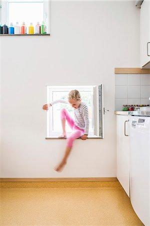 Girl entering house through kitchen window Stock Photo - Premium Royalty-Free, Code: 698-07611723