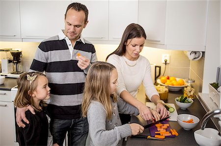 Family cutting vegetables at kitchen counter Stock Photo - Premium Royalty-Free, Code: 698-07611730