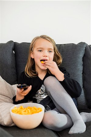 preteen open mouth - Girl eating snacks while watching TV on sofa at home Stock Photo - Premium Royalty-Free, Code: 698-07611744