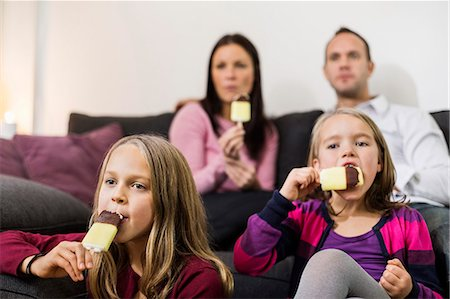 Family eating ice cream in living room Stock Photo - Premium Royalty-Free, Code: 698-07611756