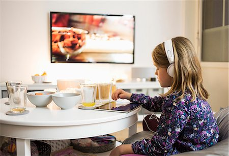 Side view of girl using digital tablet at coffee table in living room Stock Photo - Premium Royalty-Free, Code: 698-07611757