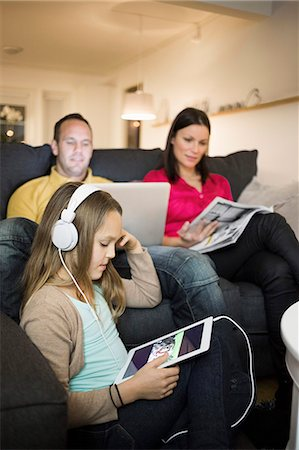 Girl listening music on digital tablet with parents in background at home Stock Photo - Premium Royalty-Free, Code: 698-07611758