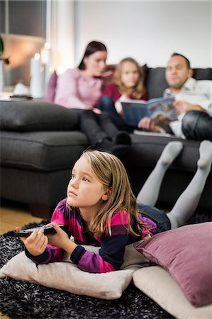 Girl watching TV on floor with family in background Stock Photo - Premium Royalty-Free, Code: 698-07611753