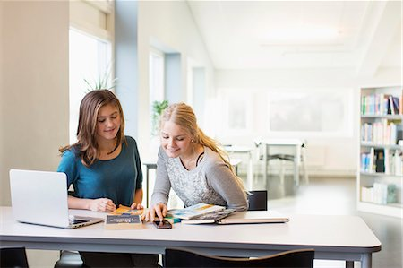Teenage girls using mobile phone at table in school library Stock Photo - Premium Royalty-Free, Code: 698-07611774