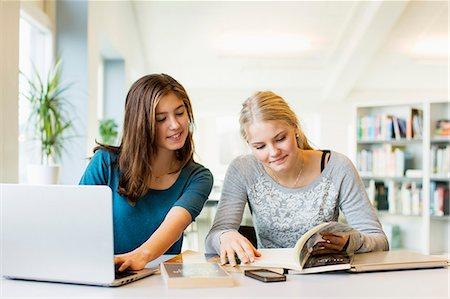 studying (all students) - Teenage girls reading book while using laptop at table in school library Stock Photo - Premium Royalty-Free, Code: 698-07611776