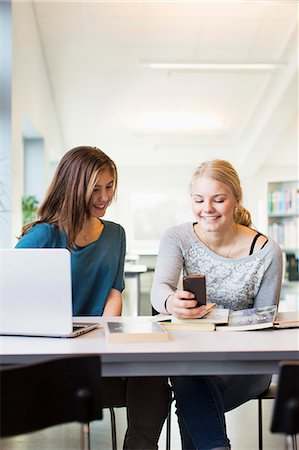 Happy teenage girls using mobile phone at table in school library Stock Photo - Premium Royalty-Free, Code: 698-07611777