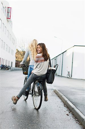 friend - Teenage girls riding bicycle on high school campus Stock Photo - Premium Royalty-Free, Code: 698-07611783