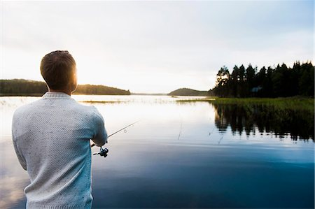 fishing - Rear view of man fishing at lake Stock Photo - Premium Royalty-Free, Code: 698-07611798