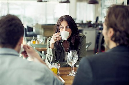 Mature woman drinking coffee while looking at colleague during lunch meeting in restaurant Stock Photo - Premium Royalty-Free, Code: 698-07611868