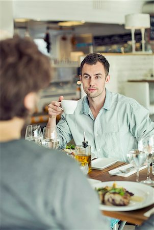 people eating at lunch - Businessman looking at colleague while having coffee in restaurant Stock Photo - Premium Royalty-Free, Code: 698-07611869