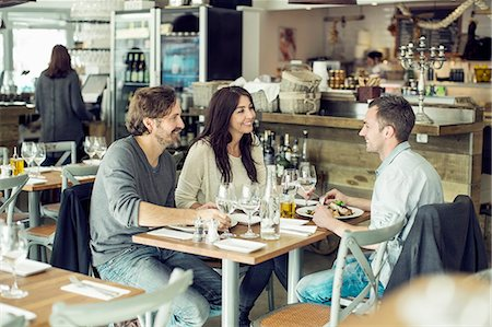 restaurant - Happy friends discussing at table in restaurant Stock Photo - Premium Royalty-Free, Code: 698-07611871