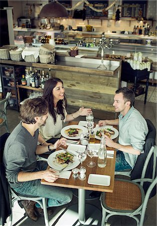 eating - Happy friends communicating in restaurant Stock Photo - Premium Royalty-Free, Code: 698-07611872