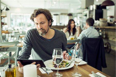 eating - Mature man using digital tablet in restaurant Stock Photo - Premium Royalty-Free, Code: 698-07611873