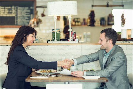 Side view of businessman and businesswoman shaking hands at restaurant table Stock Photo - Premium Royalty-Free, Code: 698-07611884