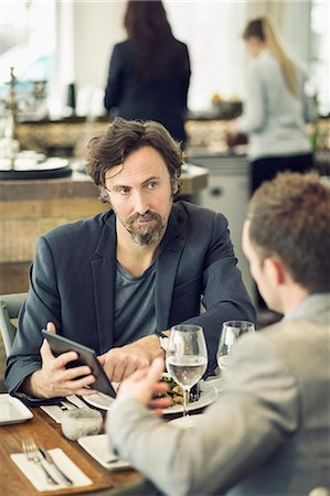 people eating at lunch - Mature businessman discussing over digital tablet with colleague at restaurant table Stock Photo - Premium Royalty-Free, Code: 698-07611887