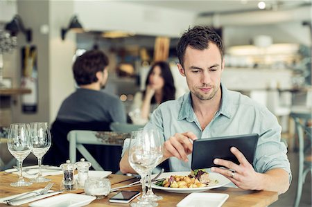 restaurant - Mid adult businessman using digital tablet while having lunch at table in restaurant Stock Photo - Premium Royalty-Free, Code: 698-07611881