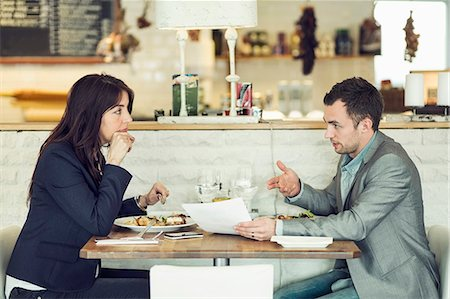 Side view of businessman with female colleague discussing paperwork at restaurant table Stock Photo - Premium Royalty-Free, Code: 698-07611882
